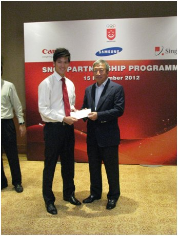 Mr Ng Ser Miang presenting the grant to Mr Derek Wong (badminton).
